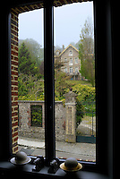 View from the window to a grand manor house and garden across the street