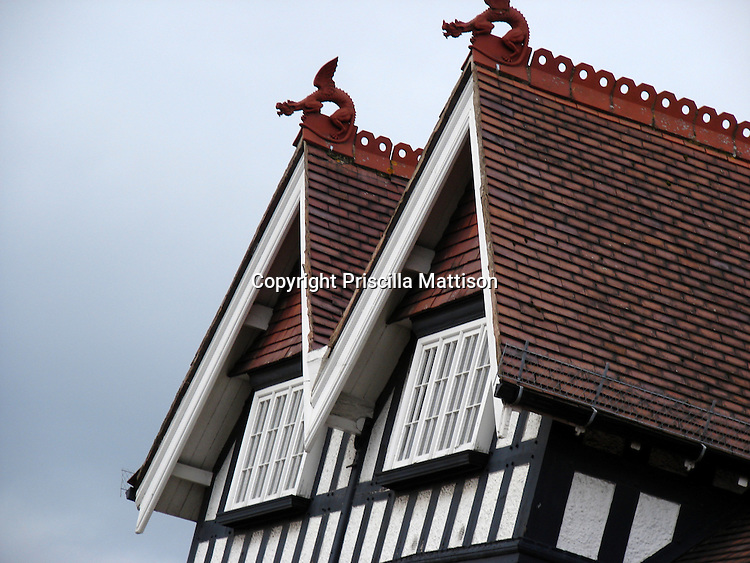 Stratford-on-Avon, England - February 3, 2008:  Winged dragons stand guard over the two peaks of a red roof on a half-timbered building.