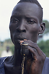 A Dinka man smokes a traditional tobacco pipe in the triple A camp ot Atepi inSudan where hundreds of Dinka tribes people seek refuge having had their villages bombed and burnt  by the Sudanese Khartoum forces.  They have travelled hundreds of miles to  avoid  hunger and death.