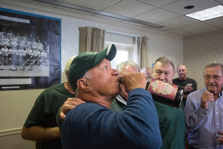 Tom Gosiorowski takes a drink from a bottle of Purple Cow Cocktail while other hockey alumni watch during the 1960s hockey alumni reunion at the OU Inn on October 1, 2016.