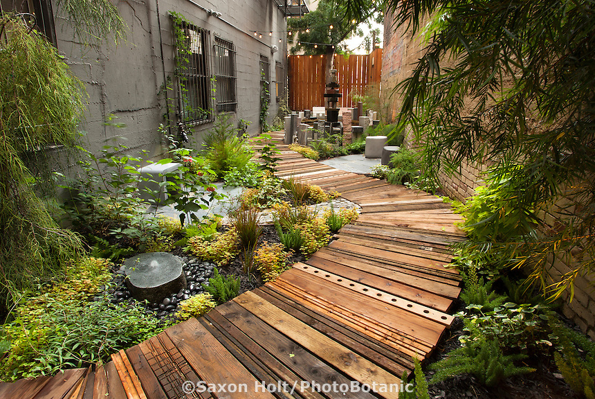 Recycled wood as boardwalk path in narrow garden. The Mark Twain Hotel design by Organic Mechanics