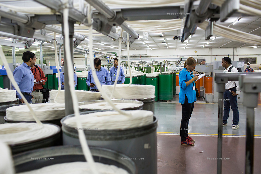 Fairtrade personnel being given a tour while Raw cotton is being processed into yarn and thread in the Spinning Room of the Pratibha vertically integrated garment unit in Indore, Madhya Pradesh, India on 11 November 2014. Photo by Suzanne Lee for Fairtrade