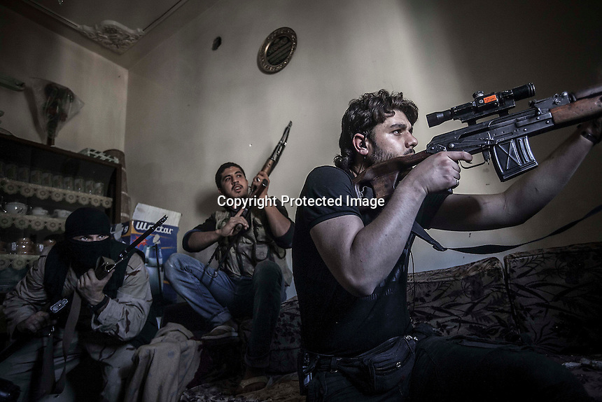 In this Monday, Oct. 29, 2012 photo, a rebel sniper aims on his enemy position as rebel fighters clash with the Syrian army in the nearby Castel Harami battlefield in the Jdeide district of Aleppo, Syria, as heavy shelling and fighting were report during the last day of Eid celebration. (AP Photo/Narciso Contreras).