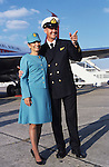 "Crew of John Travolta's jumbo jet. A  steward and stewardess on the runway tarmac...John Travolta is pilot of his very own jumbo jet, a 1964 Boeing 707-100 series. In 2003, John Travolta flew his jumbo jet around the world, in partnership with Quantas, to rekindle confidence in commercial aviation, and to remind us that elegance and style are a part of flying. The crew are dressed in tailor made authentic uniforms from the Quantas museum. The men's uniforms are styled on British Naval uniforms and the ladies' designed by Chanel. His jumbo jet sports a personalised number plate N707JT which speaks for itself. The aircraft is named ""Jett Clipper Ella"" dedicated to his son and daughter. This jumbo together with his other aircraft are housed in purpose built hangars at his home in Florida, USA."