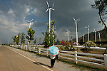 A man with an umbrella to protect from the heat admires the Kings Wind Farm in Thailand.