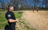 Officer David Leehans with the Bentonville Police Department stops Wednesday, March 25, 2020, to talk to a group playing volleyball at Memorial Park in Bentonville. Bentonville Parks and Recreation staff removed nets from the sand volleyball courts Tuesday and from the adjacent tennis courts Wednesday. The group found a rope nearby that they strung between the posts to act as a net. Leehans asked them to leave and they did so. Parks and recreation staff then placed signage making clear that the park was closed. All Bentonville city parks have been closed, except for the trails, to combat the spread of the covid-19 pandemic.   <br /> Go to nwaonline.com/photos to see more photos.<br /> (NWA Democrat-Gazette/Ben Goff)