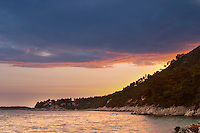 The Brna bay at sunset, bright orange sky, sky reflected in the sea water. Holiday homes on the hillside. Prizba village. Korcula Island. Prizba, Riva Apartments, Danny Franulovic. Korcula Island. Dalmatian Coast, Croatia, Europe.