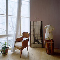 A corner of the living room with an antique torso on a wooden plinth, a contemporary photograph and a carved chair