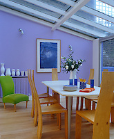 A green chair stands against a purple wall in this dining room extension