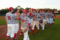 Illinois State Redbirds players, including Lucas Hall (36), Joe Kelch (3), Ryan Hutchinson (38), Brian Rodemoyer (30), and Blake Molitor (42), celebrate a victory over the Ohio State Buckeyes on March 5, 2016 at North Charlotte Regional Park in Port Charlotte, Florida.  Illinois State defeated Ohio State 5-4.  (Mike Janes/Four Seam Images)