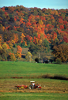 A tractor crosses a field in southern Virginia with a colorful background of fall foliage. Roanoke Virginia.