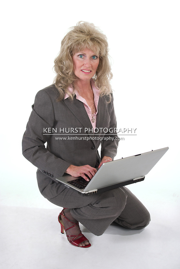 Attractive executive business woman kneeling while working on a laptop computer.