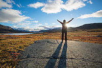Female raises hands towards sun in Autumn mountain landscape along Kungsleden trail, Lappland, Sweden