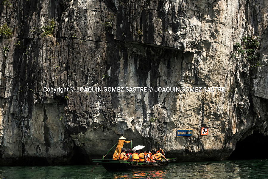 A boat with tourists goes to the entrance of Hang Luon (LUON CAVE) in the Halong Bay in Vietnam