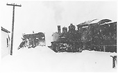 RGS K-27 #461 pushing plow-flanger #02 derailed at Ophir on track in snow storm.<br /> RGS  Ophir, CO  Taken by Reid, Homer - 1940 or 1946