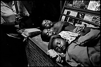 Siem Reap, Cambodia, December 2006..Three boys sleeping on a book cart in the tourist market....TB is endemic in the region, fueled by poverty, malnutrition, inadequate hygiene and the spreading of HIV/AIDS.