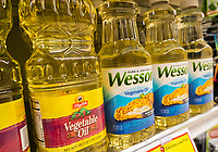Bottles of Wesson vegetable oil share space with house brand oil on a supermarket shelf in New York on Tuesday, May 30, 2017. Conagra Brands is reported to be selling its Wesson oil brand to J.M. Smucker Co. for approximately $285 million. Wesson will join Smucker's Crisco oil brand. (© Richard B. Levine)