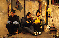 China. Old Chinese couple excluded from a changing society pass the rest of their days on the pavement outside their modest home in a Shanghai street.