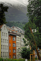 Pastel colour buildings with background of mountain and clouds. Innsbruck, Tyrol, Austria.
