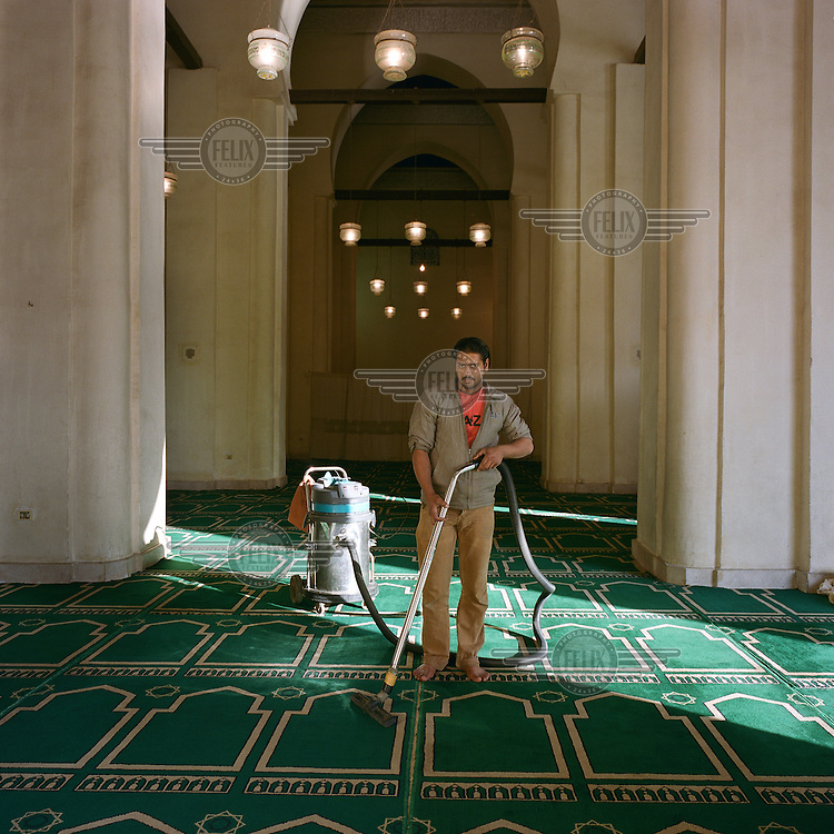 A cleaner hoovers the carpet in the Al-Hakim Mosque.