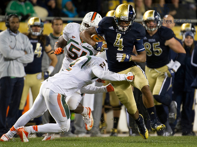 Oct. 6, 2012; Running back George Atkinson III gains 31 yards for a first down as Miami defensive back Deon Bush moves in for the tackle in the Shamrock Series at Soldier Field in Chicago. Photo by Barbara Johnston/University of Notre Dame..