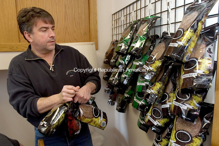 TORRINGTON, CT. 27 March 2012-032712SV02-Robert Noto, owner, chooses some product from the wall at his Tobacco shop in Torrington Tuesday. Bogie's Tobacco Factory on East Main Street in Torrington offers its customers the opportunity to purchase tobacco and machines with which to roll their own cigarettes. For $39.95 they can roll between 185 and 200 cigarettes..Steven Valenti Republican-American