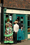 Three woman in Dickensian costume looking into bakery on Rochester High Street during Dickens Festival