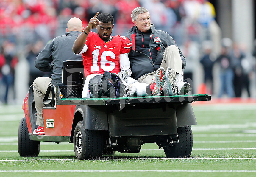 Ohio State Buckeyes quarterback J.T. Barrett (16) salutes a stadium chanting his name as a cart drives him off the field after injuring his right leg in the fourth quarter the college football game between the Ohio State Buckeyes and the Michigan Wolverines at Ohio Stadium in Columbus, Saturday morning, November 29, 2014. The Ohio State Buckeyes defeated the Michigan Wolverines 42 - 28. (The Columbus Dispatch / Eamon Queeney)
