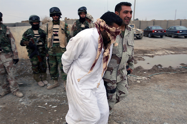 An Iraqi poice commander hauls out a captured insurgent from a police station in the town of Aitha, in northern Iraq. U.S. officers with 1st Squadron, 3rd Armored Cavalry Regiment say that an offer of amnesty under a U.S.-backed reconciliation program has convinced some Sunni insurgent leaders to lay down their arms and provide valuable intelligence on others who refuse to stop fighting. Feb. 11, 2008. DREW BROWN/STARS AND STRIPES