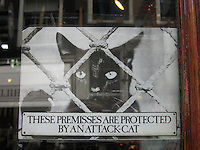 "Small funny plate inform us: ""These premisses are protected by an attack-cat"" in a shop in Amsterdam, The Netherlands, Europe"