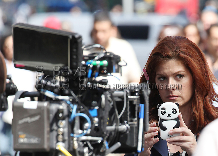 Debra Messing phjotographing with her iphone while filming a scene from the NBC TV Show 'Smash' in Times Square, New York City on September 12, 2012