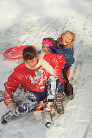 Three 13 year old friends enjoying a snowy slide on a saucer. St Paul Minnesota USA