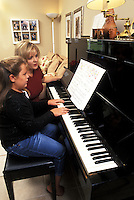 Mother teaching piano to daughter