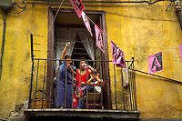 Palermo, Sicily, Italy, May 2007. A family cheers of the local football team from their balcony. The streets of Palermo are lined with historical buildings.  The rugged nature of sicily harbours beautiful villages and ruins of ancient civilizations. Photo by Frits Meyst/Adventure4ever.com