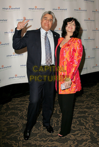 JAY LENO & MAVIS LENO.The 4th Annual Benefit Gala for Adopt-A-Minefield held at The Century Plaza Hotel in Century City, California.October 15th, 2004.full length, married, husband, wife, v sign, peace sign, gesture, red and orange fluorescent jacket, pinstripe suit.www.capitalpictures.com.sales@capitalpictures.com.©Debbie Van Story/Capital Pictures