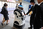 Businessmen check out Sohgo Security Services Co.'s  Reborg-Q security robot at an exhibition center in Tokyo, Japan.