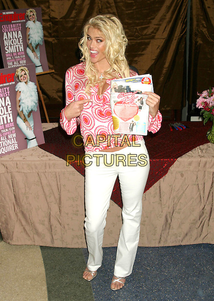 ANNA NICOLE SMITH.Signs autographs at the re-launch of The National Enquirer Hudson News in Grand Central Station, New York City, USA, April 7th 2005..full length white trousers pink red patterned shirt top printed silver strappy shoes sandals pointing magazine funny.Ref: IW.www.capitalpictures.com.sales@capitalpictures.com.©Ian Wilson/Capital Pictures.