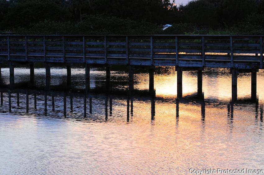 Wakodahatchee Sunset reflecting on wetlands under the boardwalk.