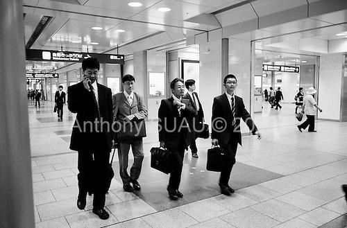 Nagoya, Japan.June 16, 2009..Businessmen arrive at the Nagoya train station in the city center.