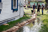 From left, Ryan Hallam, John Gamage and Bill Sandquist strategize on how best to build their sandbag wall in order to protect the home from four feet of Mississippi River floodwater in the Red Star District of Cape Girardeau, MO, on Thursday, April 28, 2011.