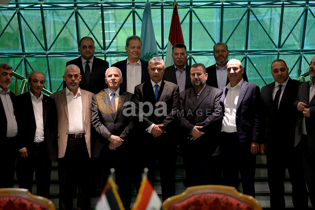 "Khaled Fawzi (C), head of the Egyptian Intelligence services, Azzam al-Ahmad (C-L), head of the Fatah delegation for the talks, and Hamas' Saleh al-Aruri (C-R) pose for a group picture with both Palestinian delegations following the signing of a reconciliation deal at the Egyptian intelligence services headquarters in Cairo on October 12, 2017, as the two rival Palestinian movements ended their decade-long split following negotiations overseen by Egypt. The new Hamas deputy leader and the head of Fatah's delegation struck the deal which was described by Palestinian Authority president Mahmud Abbas as a ""final agreement"" to end their crippling division, which has at times erupted into deadly conflict over the past ten years . Photo by STR"