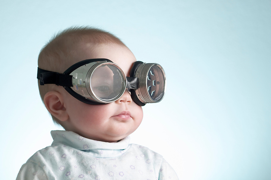 Portrait of 6 month old baby girl wearing welders goggles over eyes
