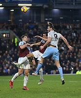 West Ham United's Andy Carroll gets in a header towards goal under pressure from Burnley's Jack Cork and James Tarkowski<br /> <br /> Photographer Rob Newell/CameraSport<br /> <br /> The Premier League - Burnley v West Ham United - Sunday 30th December 2018 - Turf Moor - Burnley<br /> <br /> World Copyright © 2018 CameraSport. All rights reserved. 43 Linden Ave. Countesthorpe. Leicester. England. LE8 5PG - Tel: +44 (0) 116 277 4147 - admin@camerasport.com - www.camerasport.com