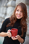 beautiful young woman with long brown hair smiles and holds a coffee cup outdoors in morning shade