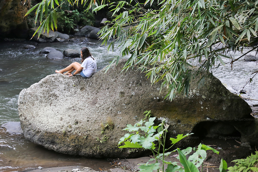 A student relaxes on a rock in the Ayung River<br />