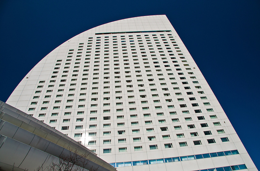 Distinctive curve of the Yokohama Intercontinental Hotel set against a deep blue sky.