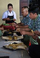 Jatiluwih, Bali, Indonesia.  Putting Chicken on Skewers in Preparation for Chicken Satay.