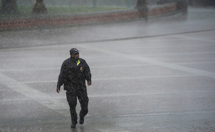 UNITED STATES - JUNE 13: A U.S. Capitol Police officer heads for cover as a strong line of thunderstorms pelts the Capitol with heavy rain and winds on Thursday, June 13, 2013, in the Capitol. (Photo By Bill Clark/CQ Roll Call)