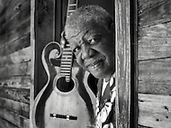 The late Macavine Hayes stands in a doorway with his acoustic guitar.