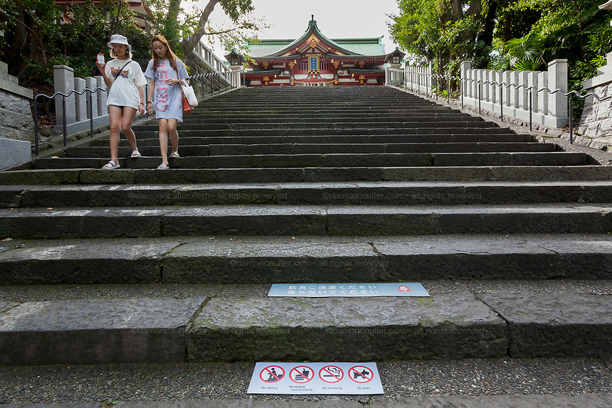 Chinese tourists on steps at Hie Shrine with signs warning visitors about the shrine rules. Hie Shrine, Akasaka, Tokyo, Japan. Friday September 7th 2018